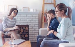 Mother and her male youngster attending psychologist. Problem within our family. Female professional psychotherapist taking notes while listening a mother of her Stock Photography