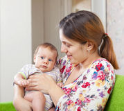 Mother with her 3 month daughter. In home interior royalty free stock photo