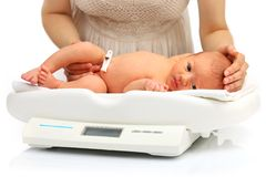 Mother and her newborn baby on a weight scale Royalty Free Stock Photo