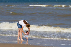 Mother and her newborn daughter for the first time on beach Royalty Free Stock Photos