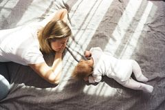 Mother with her newborn son lay on the bed in the rays of sunlight stock photos