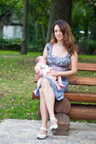 Mother and her newborn son. On a park bench Stock Photography