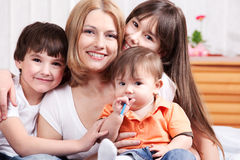 Mother and her  offsprings. Mother and her three offsprings in the bedroom Stock Photo