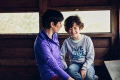 Mother with her seven year old daughter laughing in a cabin in the countryside stock photography
