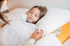 Mother with her sick kid at home. Mother taking care of her sick daughter in bedroom Stock Image