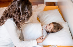 Mother with her sick kid at home Stock Photos