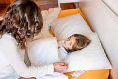 Mother with her sick kid at home. Mother taking care of her sick daughter in bedroom Royalty Free Stock Image