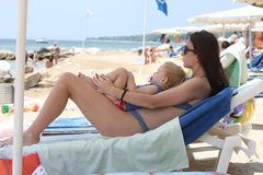 Mother and her sleeping baby girl. Cute baby girl with her mother sleeping on the beach Stock Images
