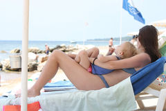 Mother and her sleeping baby girl. Cute baby girl with her mother sleeping on the beach Stock Photos