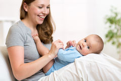 Mother with her small baby in nursery room Stock Photography