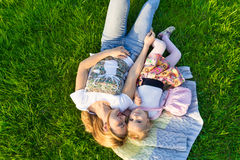 Mother and her small daughter lying on green lawn Stock Photo