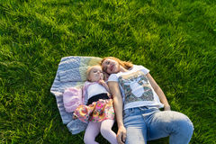 Mother and her small daughter lying on green lawn Stock Photography