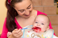 Mother with her snotty son. Mother is spoon feeding her snotty half year old son with beetroot puree Stock Image