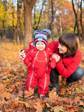Mother with her son in the autumn park Stock Images