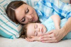 Mother and her son baby sleeping together in a bedroom. Cute mother and her son baby sleeping together in a bedroom royalty free stock photos