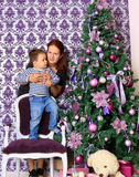 Mother and her son in the Christmas Corner. In lilac tones Royalty Free Stock Image