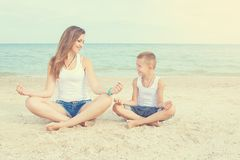 Mother and her son doing yoga on coast of sea on beach. Royalty Free Stock Images