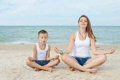 Mother and her son doing yoga Stock Photos