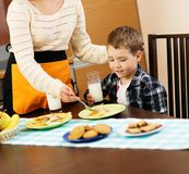 Mother and her son eating breakfast Stock Images