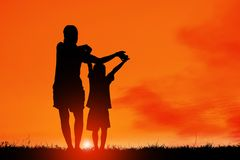 Mom and son having fun at sunset,  family a happy time, Asian kid,Silhouette a kid at the sunset. Stock Photos