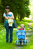 Mother and her son on footpath in park. Young mother and her son one-year-old on footpath in park with carriage. Summer time Stock Photo