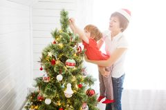 Mother with her son on hands decorating Christmas tree royalty free stock photo