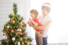 Mother with her son on hands decorating Christmas tree together royalty free stock images