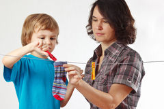 Mother with her son hanging clothes Stock Photography