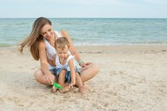 Mother and her son having fun on the beach Stock Images