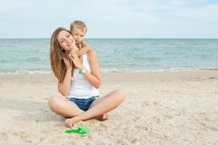 Mother and her son having fun on the beach Stock Photo