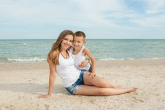 Mother and her son having fun on the beach Stock Photos