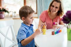 Mother and her son having fun decorate eggs stock photos