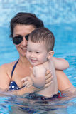 Mother and her son having fun in a swimming pool. Young mother and her son having fun in a swimming pool Royalty Free Stock Image
