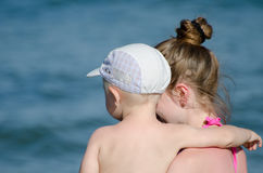 Mother with her son in her arms in a swimsuit watching the sea, close up Royalty Free Stock Image