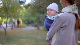 Mother with her son in her arms walking in the park. Close-up. Mother with her son in her arms walking in the park stock footage