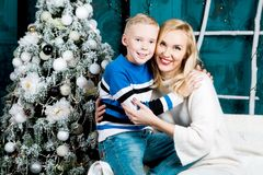 Mother and her son at home with a Christmas tree stock image