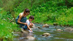 Mother with her son are launching the paper boat on a water Royalty Free Stock Photography