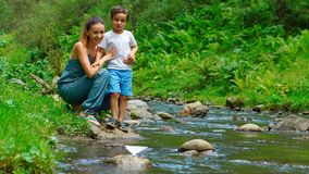 Mother with her son look at the toy paper boat on a stream Stock Image
