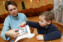 Mother with her son making paper snowflakes Stock Photo