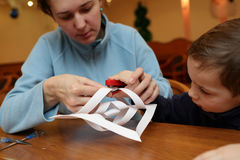 Mother and her son making paper snowflakes Stock Photography