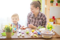Mother and her son painting colorful easter eggs. Family celebrating Easter. Parent and kid play indoors. Decorated home and sprin. G flowers Stock Image