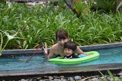 Mother and her son are palying at pool side Royalty Free Stock Photo
