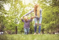 Mother with her son in park teaching his first steps. stock images