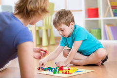 Mother and her son playing in board game. On floor in nursery Royalty Free Stock Photography