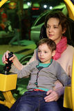 Mother with her son playing helicopter simulator Stock Image