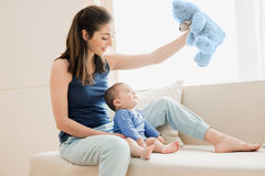 Mother and her son playing with teddy bear. Young family concept. Beautiful mother and her son playing with teddy bear. Young family concept Stock Image