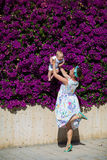 Mother and her son plays near blooming bush Stock Photography