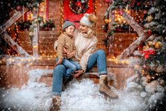 Sitting on the porch. Mother and her son are on the porch of their house decorated for Christmas. Family miracle time. Merry Christmas and Happy New Year royalty free stock photography