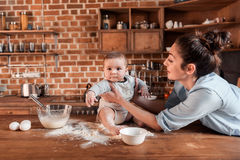 Mother with her son preparing dough for cookies and having fun together at the kitchen. Happy mother with her son preparing dough for cookies and having fun Stock Photos