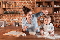 Mother with her son preparing dough for cookies and having fun together at the kitchen. Happy mother with her son preparing dough for cookies and having fun Stock Images